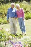 Couples aînés marchant dans le jardin Image stock