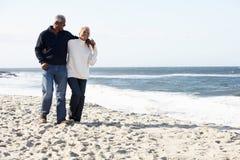 Couples aînés marchant le long de la plage ensemble Photographie stock libre de droits