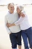 Couples aînés marchant le long de la plage ensemble Photo libre de droits