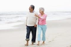 Couples aînés marchant le long de la plage ensemble Image libre de droits