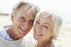 Couples aînés marchant le long de la plage ensemble Images stock