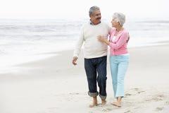 Couples aînés marchant le long de la plage ensemble Photos libres de droits