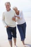 Couples aînés marchant le long de la plage ensemble Images libres de droits