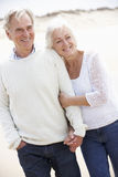 Couples aînés marchant le long de la plage ensemble Image stock
