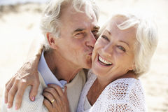 Couples aînés marchant le long de la plage ensemble Photographie stock