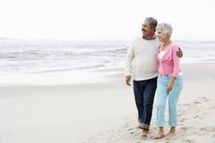 Couples aînés marchant le long de la plage ensemble Photos stock
