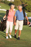Couples aînés marchant le long du terrain de golf Images libres de droits