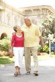 Couples aînés marchant par la rue de ville Image stock