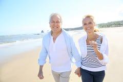 Couples aînés marchant sur la plage Images libres de droits