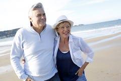 Couples aînés marchant sur la plage Photographie stock libre de droits