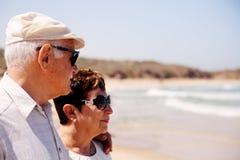 Couples aînés marchant sur la plage Image stock