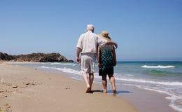 Couples aînés marchant sur la plage Photos stock