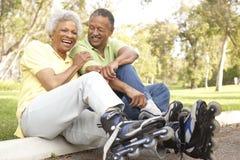 Couples aînés mettant en fonction dans la ligne patins en stationnement Photos stock