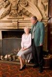 Couples aînés par la cheminée Photos stock