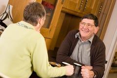 Couples aînés parlant dans la cuisine Photo stock