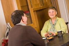 Couples aînés parlant ensemble dans la cuisine Image stock