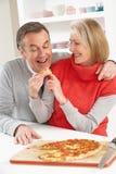 Couples aînés partageant la pizza à emporter dans la cuisine Photos stock