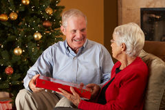 Couples aînés permutant des cadeaux Image libre de droits