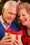 Couples aînés permutant des cadeaux de Noël Images stock
