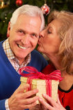 Couples aînés permutant des cadeaux de Noël Image stock
