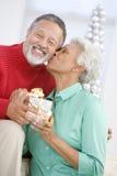 Couples aînés permutant un cadeau de Noël Photos libres de droits