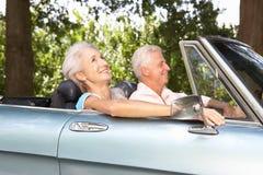 Couples aînés pilotant dans une voiture de sport Images libres de droits