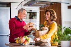 Couples aînés préparant la nourriture dans la cuisine Photos stock