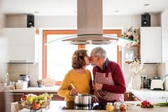 Couples aînés préparant la nourriture dans la cuisine Photos libres de droits