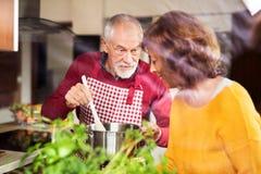 Couples aînés préparant la nourriture dans la cuisine Images stock