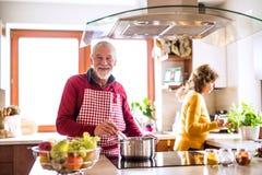 Couples aînés préparant la nourriture dans la cuisine Image libre de droits