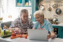 Couples aînés préparant la nourriture images stock