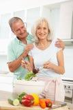 Couples aînés préparant la salade dans la cuisine moderne Photo libre de droits