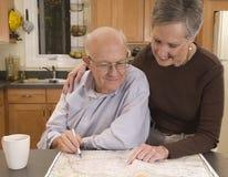 Couples aînés prévoyant un voyage Images stock