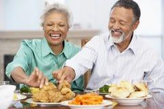 Couples aînés prenant le déjeuner à la maison Images libres de droits