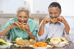 Couples aînés prenant le déjeuner à la maison Images stock