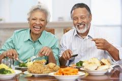 Couples aînés prenant le déjeuner à la maison Image stock