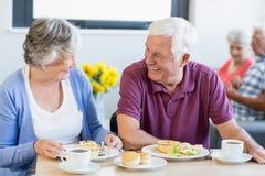 Couples aînés prenant le déjeuner ensemble Photos stock