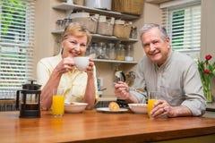Couples aînés prenant le petit déjeuner ensemble Image stock