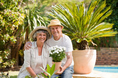 Couples aînés regardant l'appareil-photo dans le jardin Photo libre de droits