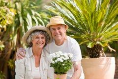 Couples aînés regardant l'appareil-photo dans le jardin Images stock