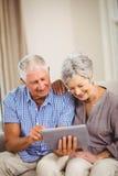 Couples aînés regardant la tablette digitale Photographie stock libre de droits