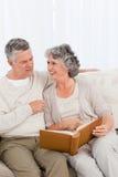 Couples aînés regardant leur album photos Photos stock