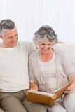 Couples aînés regardant leur album photos Photos libres de droits