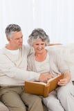 Couples aînés regardant leur album photos Photo stock
