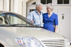 Couples aînés restant à côté du véhicule Photo stock
