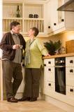 Couples aînés riant ensemble dans la cuisine Photographie stock