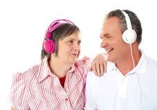 Couples aînés romantiques appréciant la musique ensemble Photographie stock