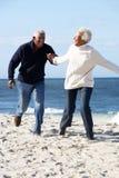 Couples aînés romantiques fonctionnant le long de la plage Images libres de droits