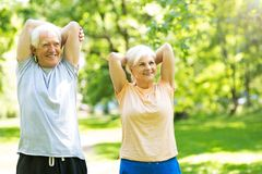 Couples aînés s'exerçant en stationnement Photos stock