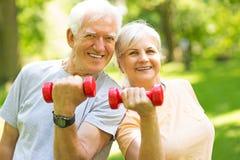 Couples aînés s'exerçant en stationnement Photographie stock libre de droits